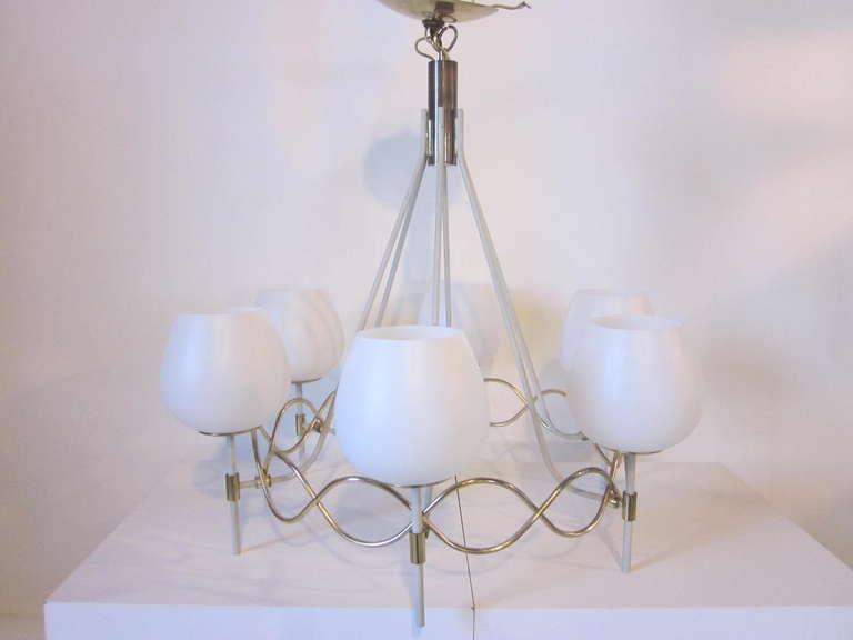 A midcentury chandelier with six white globes sitting on wave like sinusoid- sphere brass metalwork with radiating hanging rods fusing at the top into a shaft of bronze. Retains the original manufactures paper label and matching brass ceiling cap.