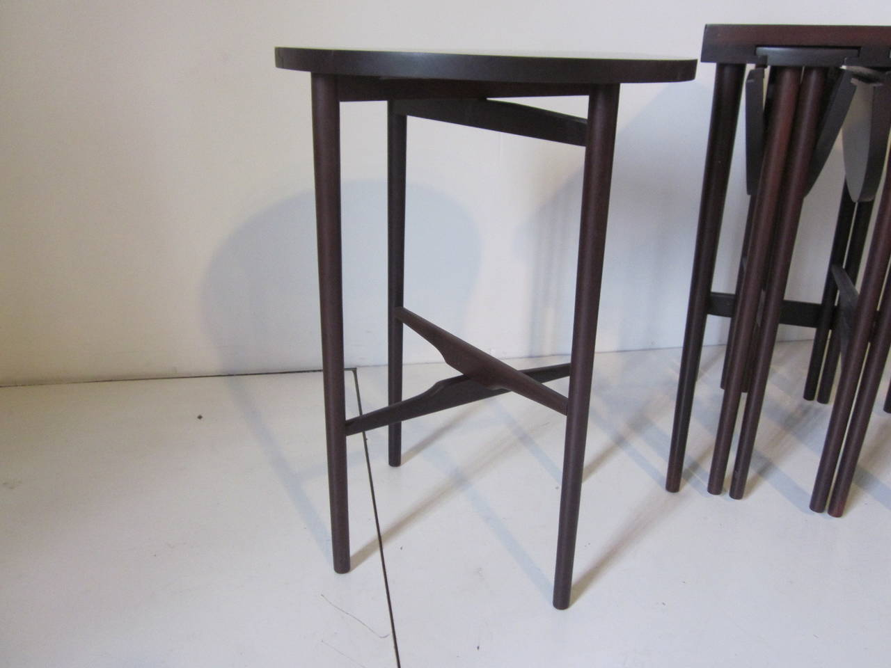 A great nesting table set with four fold up round side tables that slide and hang in a larger side table that is finished in a dark ebony tone. Retains the original tag to the bottom Singer and Sons New York, Chicago. The small tray table size is