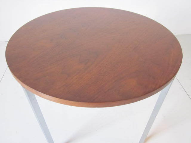 A walnut topped side table with a square tubular steel base finished in brushed chrome, designed by Florence Knoll and retains early manufactures label to the bottom .