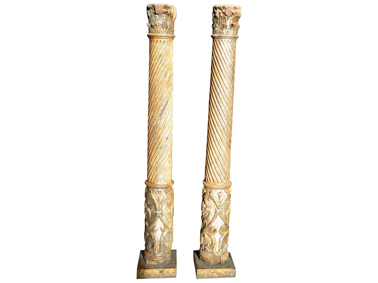 A stunning pair of 17th century Spanish Colonial wooden columns beautifully carved and adorned with cherubs and bunches of grapes. These spectacular columns retain a good bit of the original silver gilt and polychromed finish.