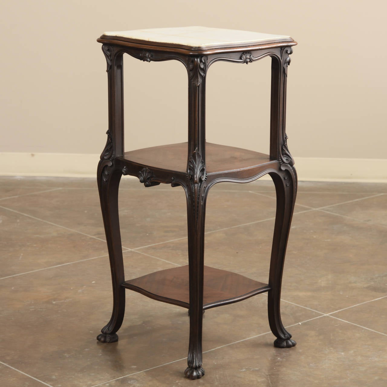Handcrafted from exotic imported rosewood and fitted with a contoured onyx top, this stunning antique 19th century French nightstand can easily double as a lamp table, adding flair and style to any room! The three-tiered design with its subtly yet