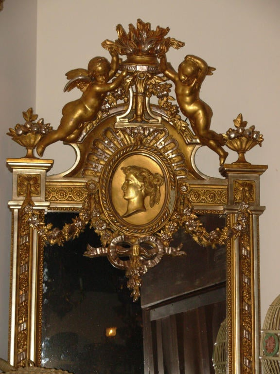 A most ornate American gilt mirror, in the Renaissance Revival style, attributed to Gustave Herter, with full bodied cherubs atop a portrait bust of a woman done in the neo grec style, with baskets of fruits and flowers and ribbons and it is