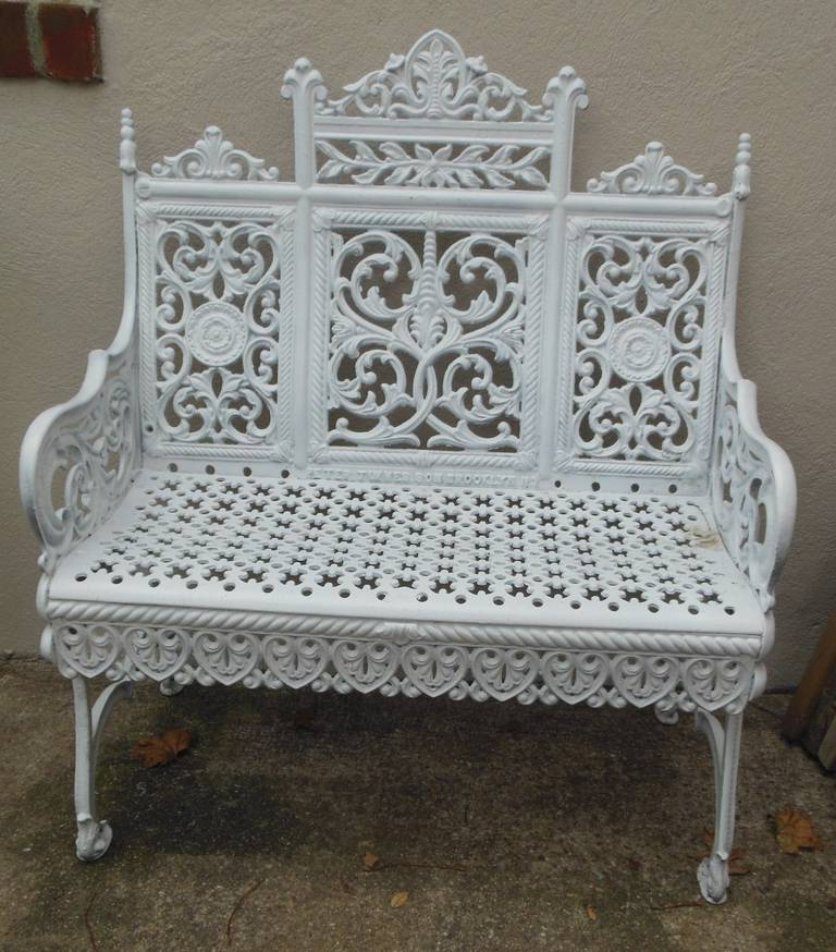 A fancy cast iron garden bench made in Brooklyn New York and patent dated 1895 by Peter Timmes Son. This filigree patterned bench is the most elaborate of a school of benches made in New York City in the late 19thC and commonly referred to as the