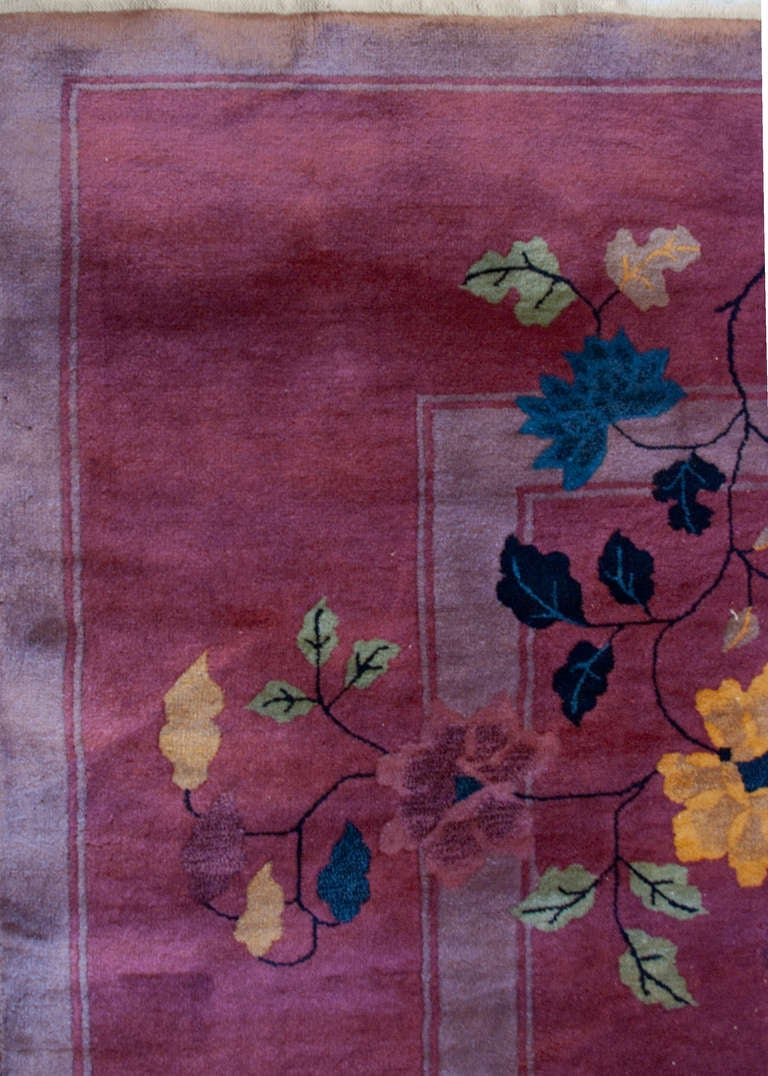 An early 20th century Chinese Art Deco rug with a rich fuchsia background and asymmetrical multicolored floral pattern.