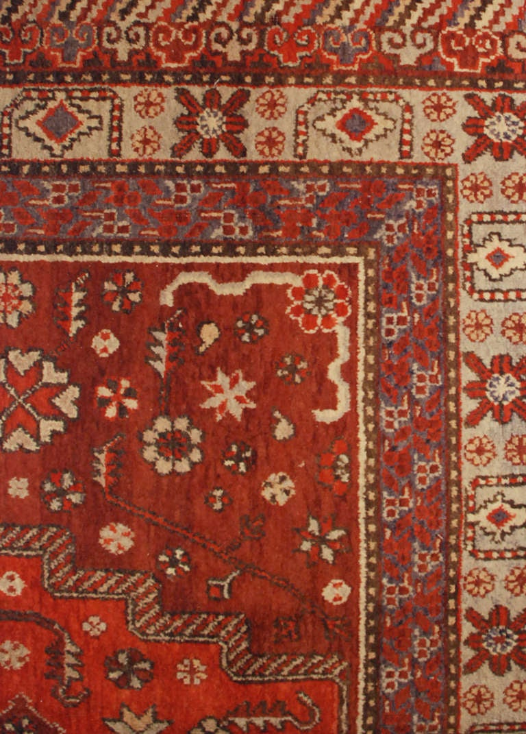 An antique, early 20th century, central Asian Samarkand rug with unusual diamond medallion amidst a field of flowers on a crimson background, surrounded by multiple contrasting floral borders.  Measure: 6'2