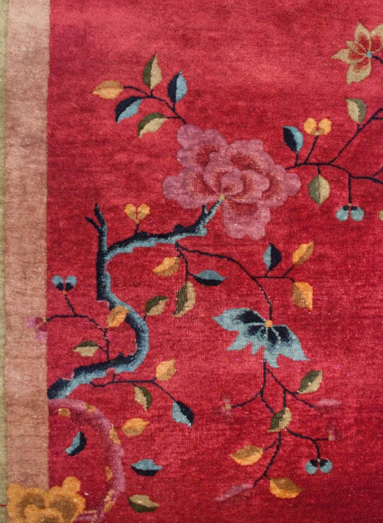 A Chinese Art Deco rug with a cranberry background covered with an all-over multicolored floral pattern surrounded by a pale green border.