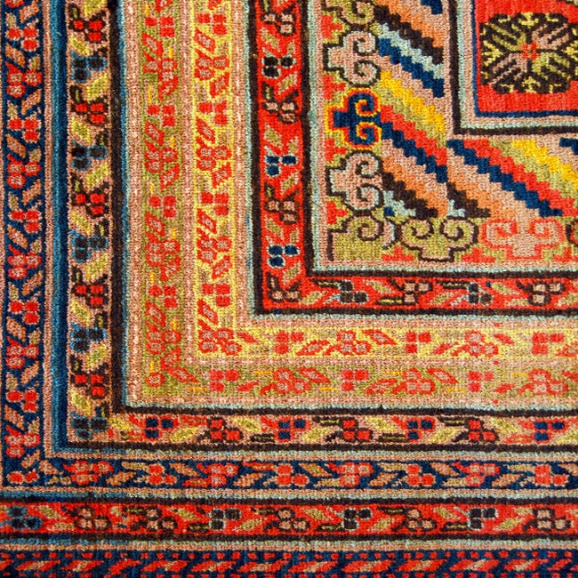 A 19th century Central Asian Samarghand carpet with one central medallion surrounded by pomegranates and other floral motifs on an indigo background surrounded by a multi layered contrasting border.    Measures: 7' x 14'.      Keywords: