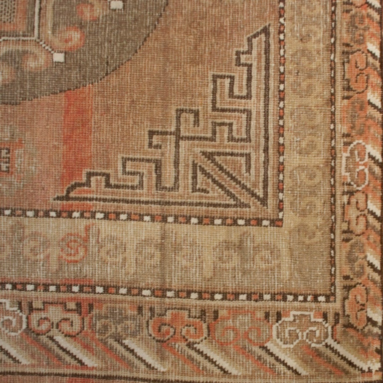 A 19th century Central Asian Samarghand carpet with three central medallions on a field of muted red surrounded by a series of contrasting borders.    Measures: 5' x 11'.      Keywords: Rug, carpet, textile, Persian, Azeri, Heriz, tribal,