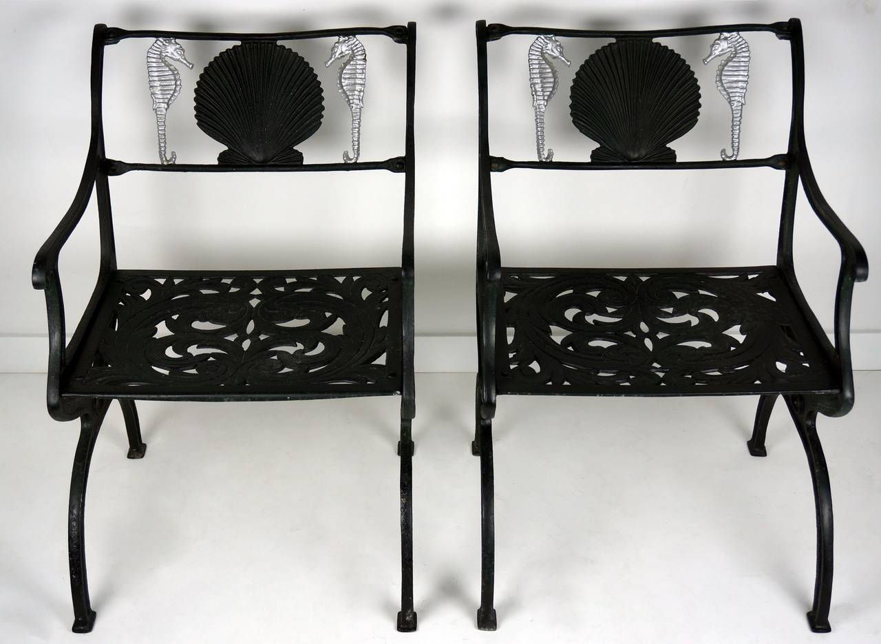pair of cast aluminum garden chairs with seahorse and shell motif
