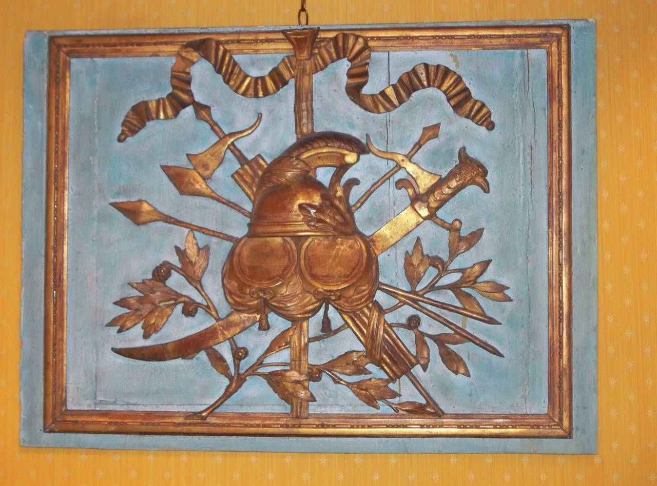 Overall probably an allegory of might or strength. Instruments of war with oak leaves and acorns (oak being a very strong wood). Cut from paneling or from a trumeau, architectural fragment. 