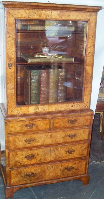 A diminutive bureau bookcase cabinet with stunning veneers /solid walnut boards. Truly magnificent colors and patina, mottled fading throughout. Mellow, warm ,faded appeal. Beveled glass door. Rare small size, basically a book cabinet on a walnut