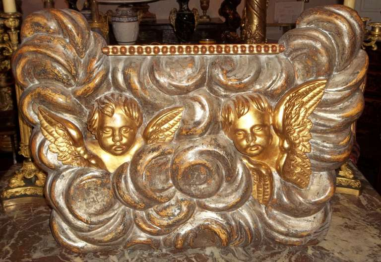 A large fragment or plaque in silver and gold gilt leaf possibly altar piece.   Two very well carved putti or cherubs ( maybe angels )in fine matte and water gilt (full relief ) peeking through the clouds in celestial flight. The wings are in