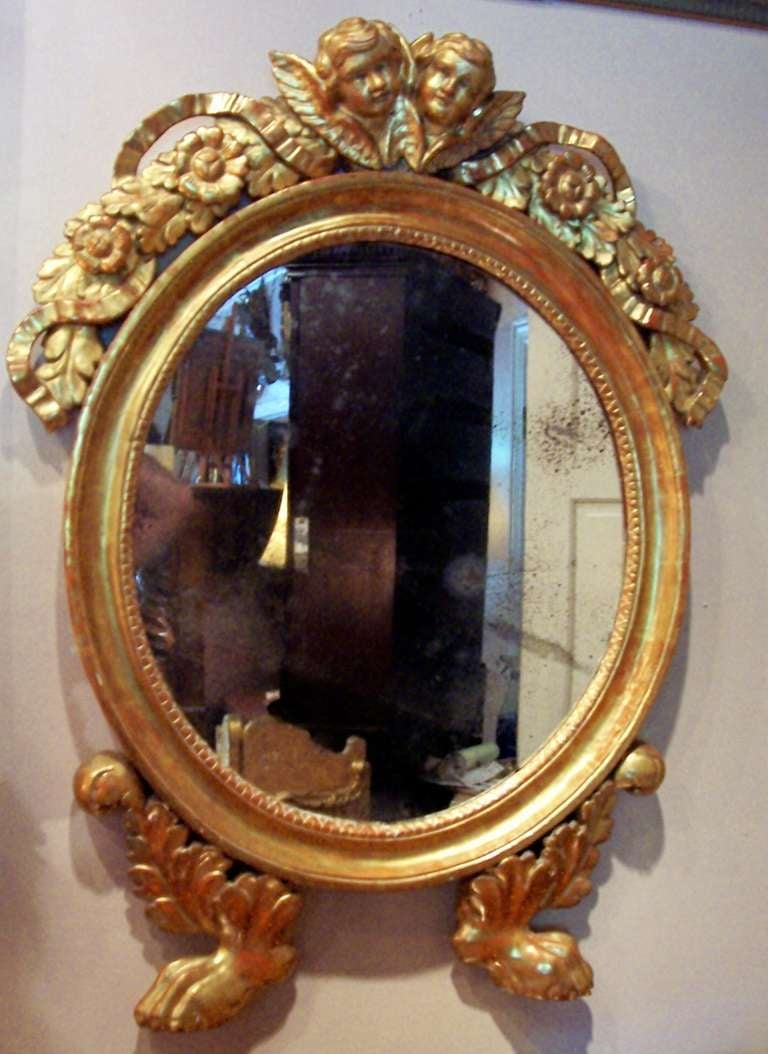 An oval giltwood mirror with elaborate cresting of putti or cherubs amidst a festoon of intertwining ribbon and flowers. The bottom with  hairy paw feet. The gilt a lemony color with a Venetian red-orange bole bleeding through out. Nicely