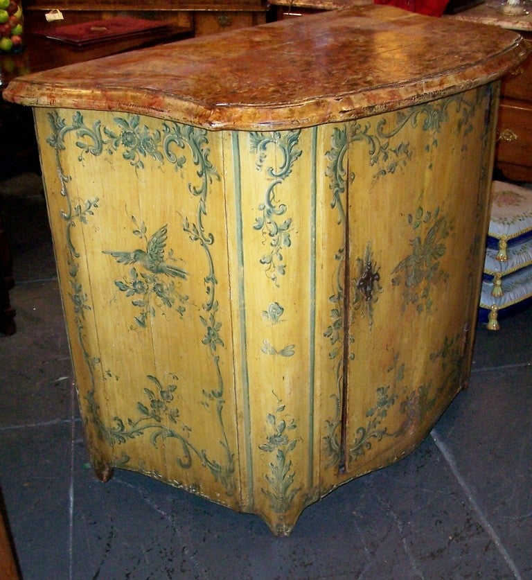 A yellow ground cabinet with blue or green 'C' and 'S' scrolls painted decoration with a bird centered on a branch. In the more Provincial areas these cupboards took the place of a commode or a chest for both utility and decorative effect. The large