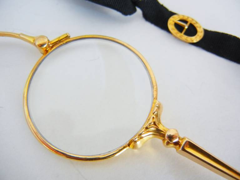 This stylish 14-karat yellow gold, snap-open or fold-close, lady's lorgnette is designed to wear as an accessory around the neck for reading theatre or opera programs and menus in dark restaurants. The tapering handle ends in a heart-shaped ring. It