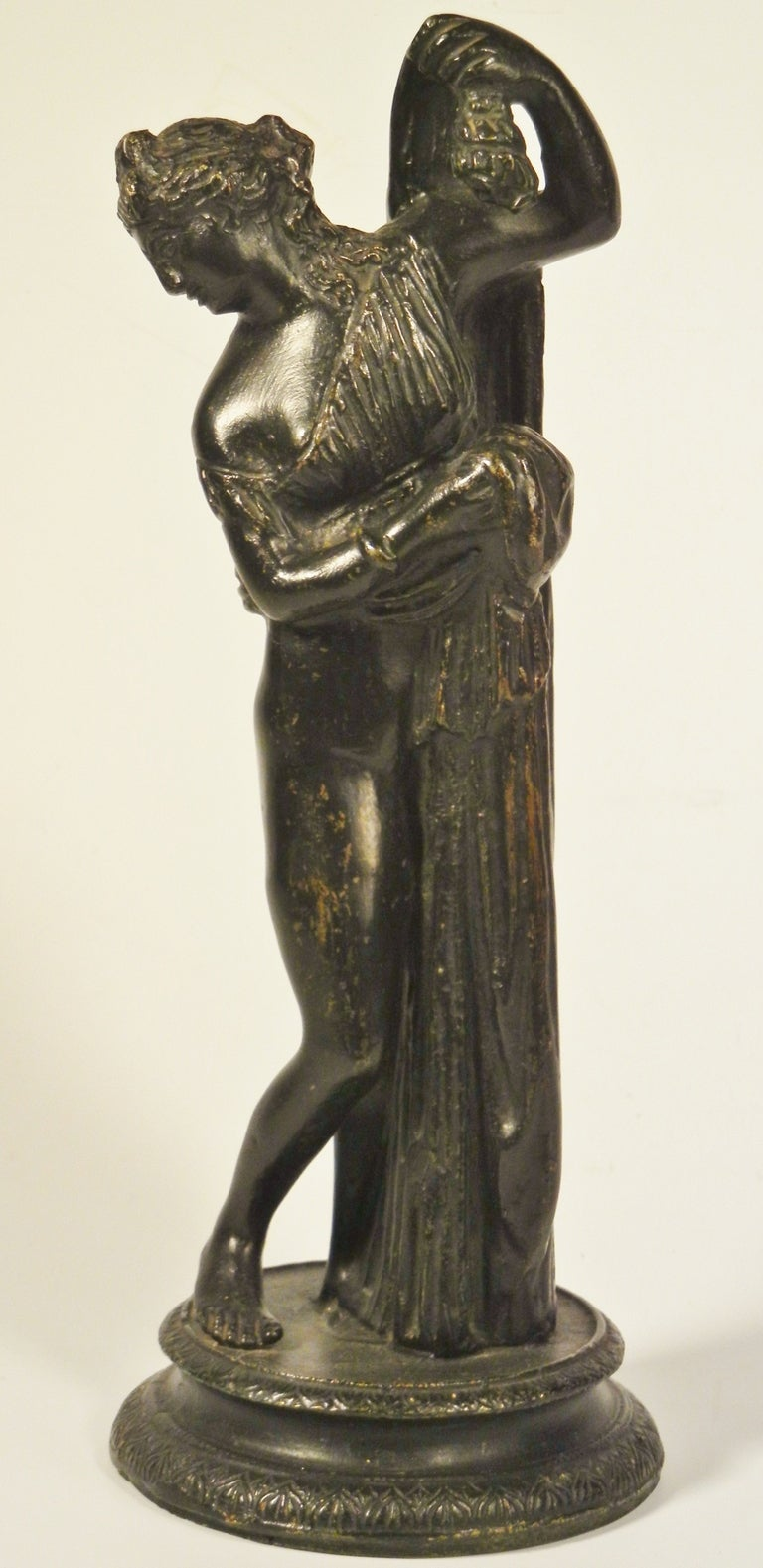 This graceful tabletop bronze figure with its black patina depicts the