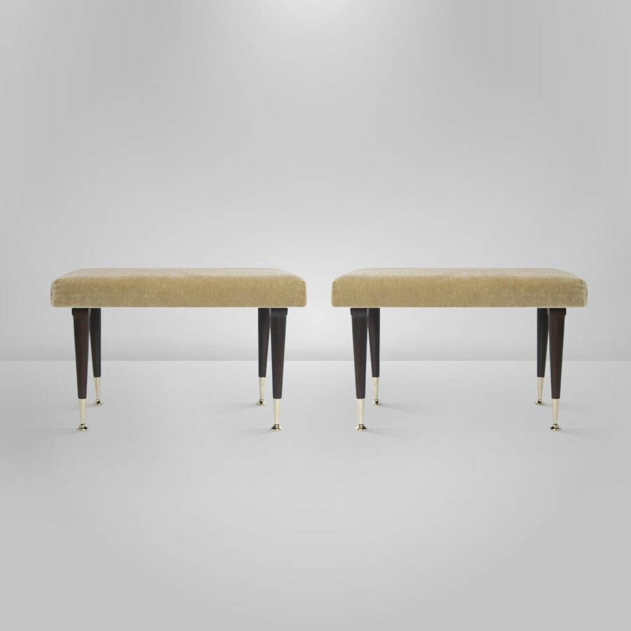 Pair of Mid-Century Modern stools by Swedish furniture designer Edmond J. Spence . Newly upholstered in natural mohair. Walnut legs newly refinished in dark, brass sabots newly polished.