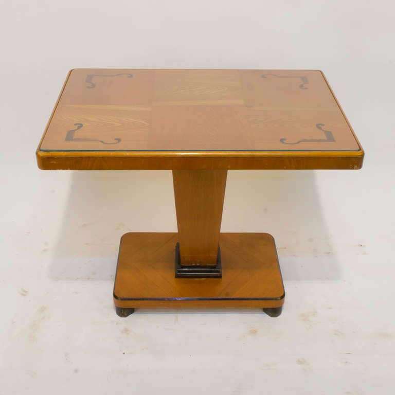 A rectangular, pedestal table, designed with a raised lip, and conveniently fitted with an articulated glass top with ground edges, to protect the decorative inlay of birch and ash. Typical of the Art Deco era in Sweden, the table incorporates