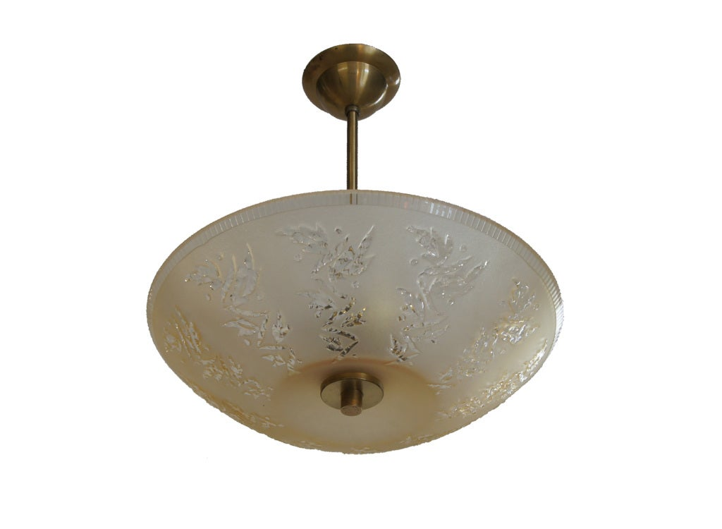 A golden toned art glass light fixture which is moulded, then etched and finally carved with stylized leaves and vines.