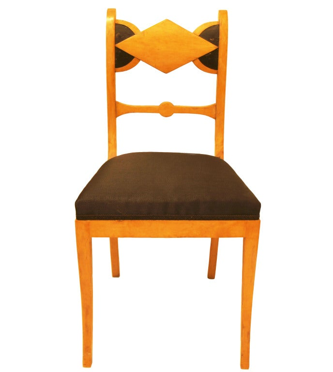 Sturdy and elegant, featuring caramel-stained birch juxtaposed with ebonized carved back rests, saber legs and horsehair seats.