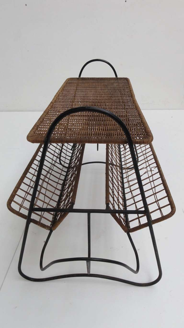 A beautiful French 1950s small side table with magazine reck in black enameled metal rod and original wicker.<br /> <br /> Nicely organic shaped and transparent French design in the style of Raoul Guy<br /> <br /> There are a few minor damages to