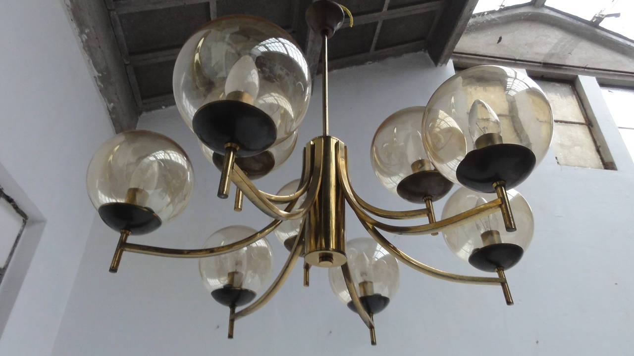 A very nice looking 50's brass Italian chandelier with 9 glass globes with a transparent gold finish