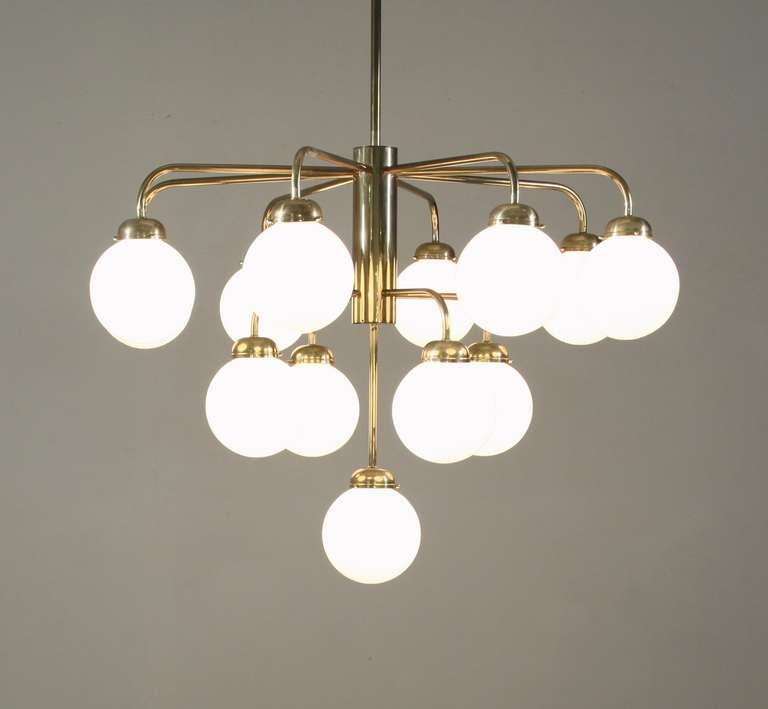 A large German brass chandelier from the 1960s. This chandelier is attached to the ceiling with a long stem and has 13 arms on three different levels. Each arm holds an opaline globe shade. 