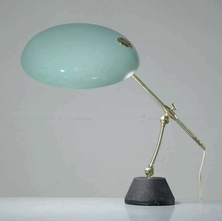 A Swiss desk lamp by/in the manner of BAG Turgi. The lamp has a green lacquered metal shade on a brass rod and cast iron foot. The height of the lamp is adjustable between 36 and 55 cm and the shade can be turned at approximately 45 degrees.