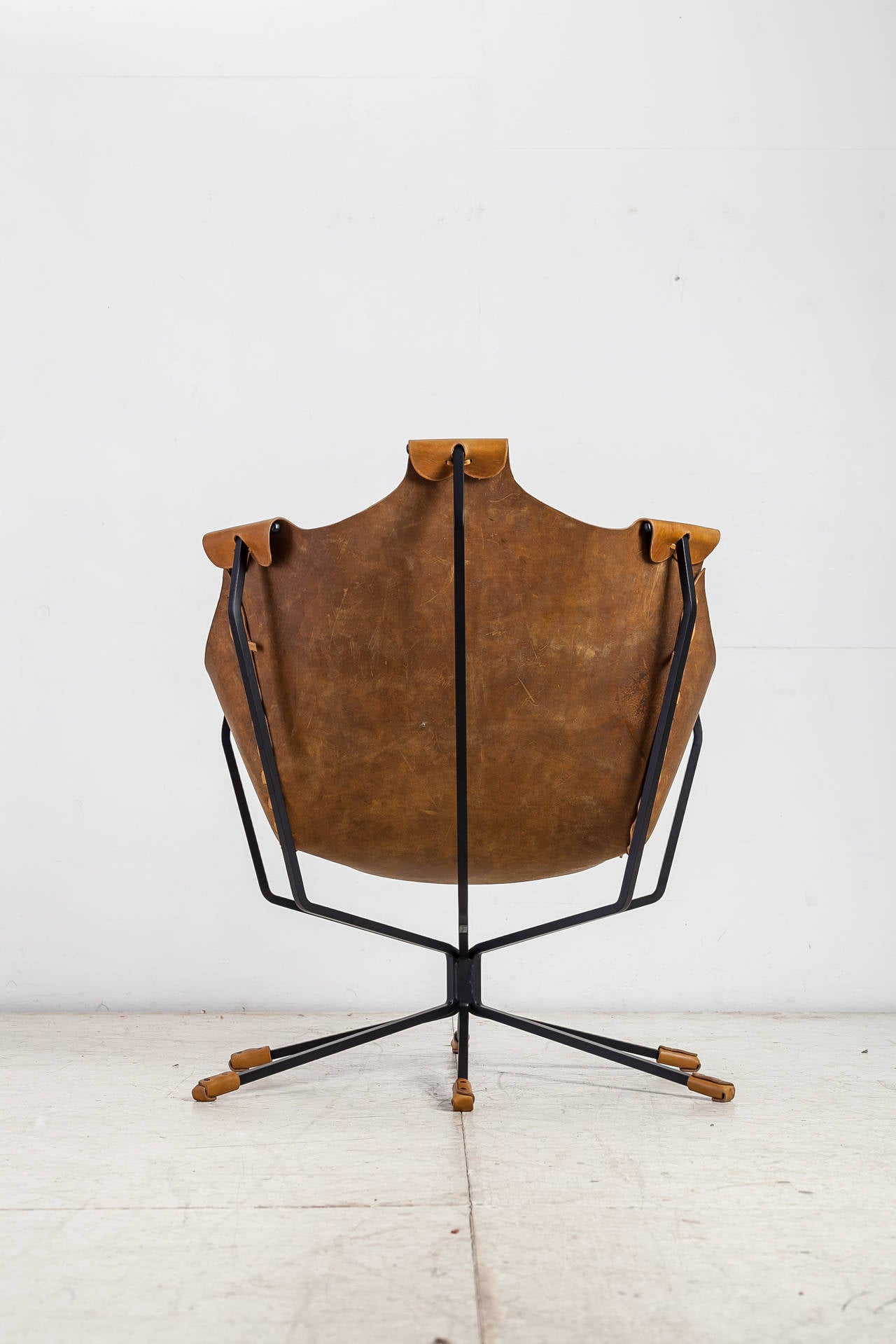 A model 'Flight of Fancy' sling chair by American designer Daniel Wenger. The chair is made of black steel frame with six legs, that come together in the middle and then spread out again. Hanging from the frame is brown leather seating. The seating