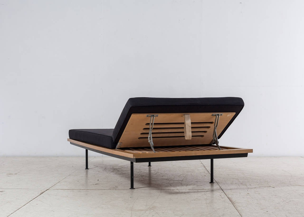 A beautiful daybed from the 1950s by Swiss designer Kurt Thut. The daybed is made of a wooden frame with adjustable headrest, standing on four black lacquered metal feet. The mattress has been newly upholstered.