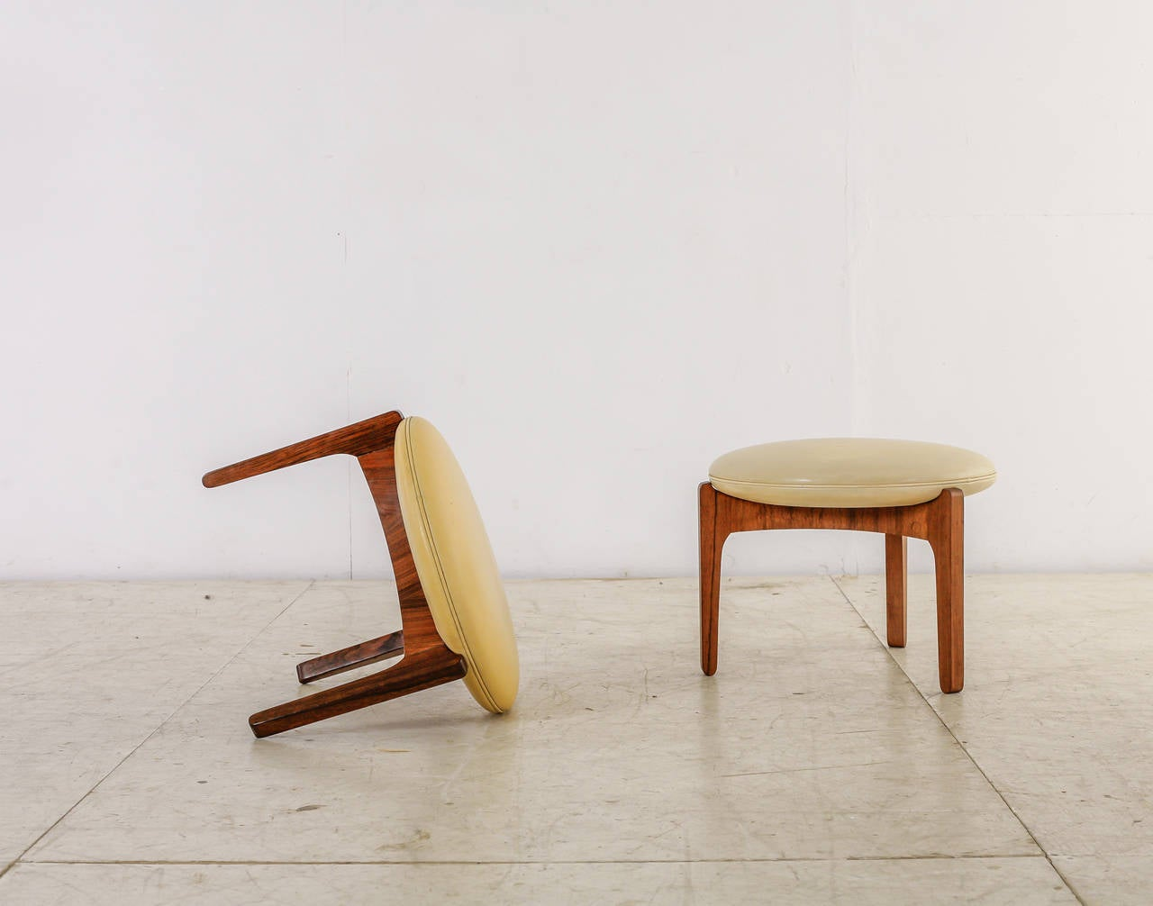 A pair of Danish 1960s tripod stools made of a rosewood frame with a leather cream colored cushion. Designed by Sven Ellekaer for Chr. Linneberg Møbelfabrik in 1962.  The stools have some minor wear, but are in an overall good condition. There are