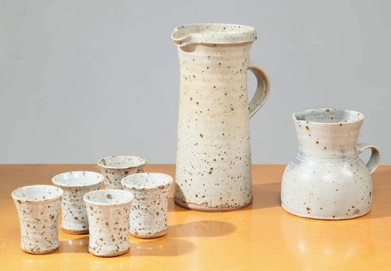 A set of two ceramic pitchers and five cups by the French ceramist, sculptor and painter Gustave Tiffoche in wonderful earth tones.  Marked by Tiffoche underneath.  Dimensions: High pitcher: 27.5 cm height, 17 cm depth and 12.5 cm width Lower