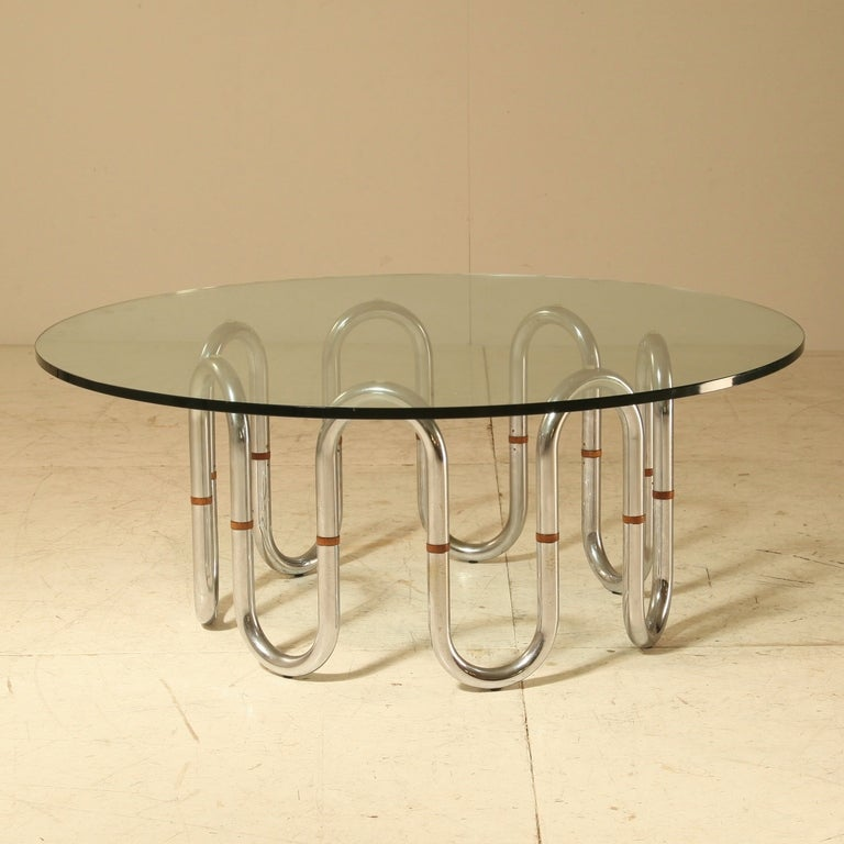 A rare sidetable with a tubular chrome frame and a thick glass top, from the late 1960s. The frame has decorative wooden connections and is semi-flexible; it can be placed in a round or oval shape. Mint condition. This item is curated for you by