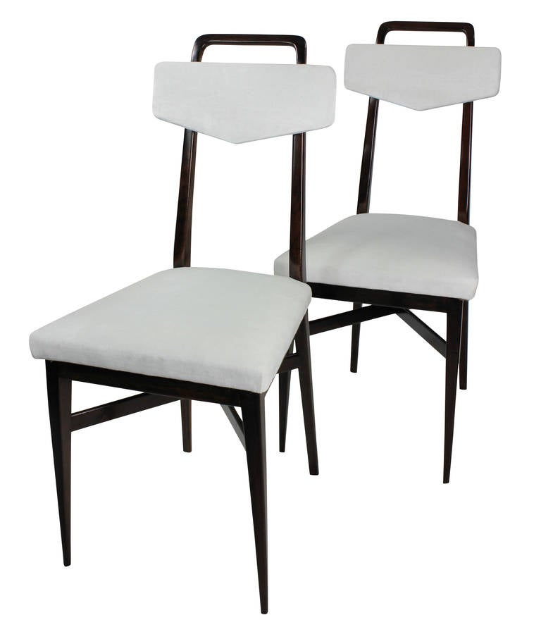 A set of four Italian dining chairs in the manner of Parisi in solid mahogany with over stuffed seats and backs in white velvet. With brass detail.