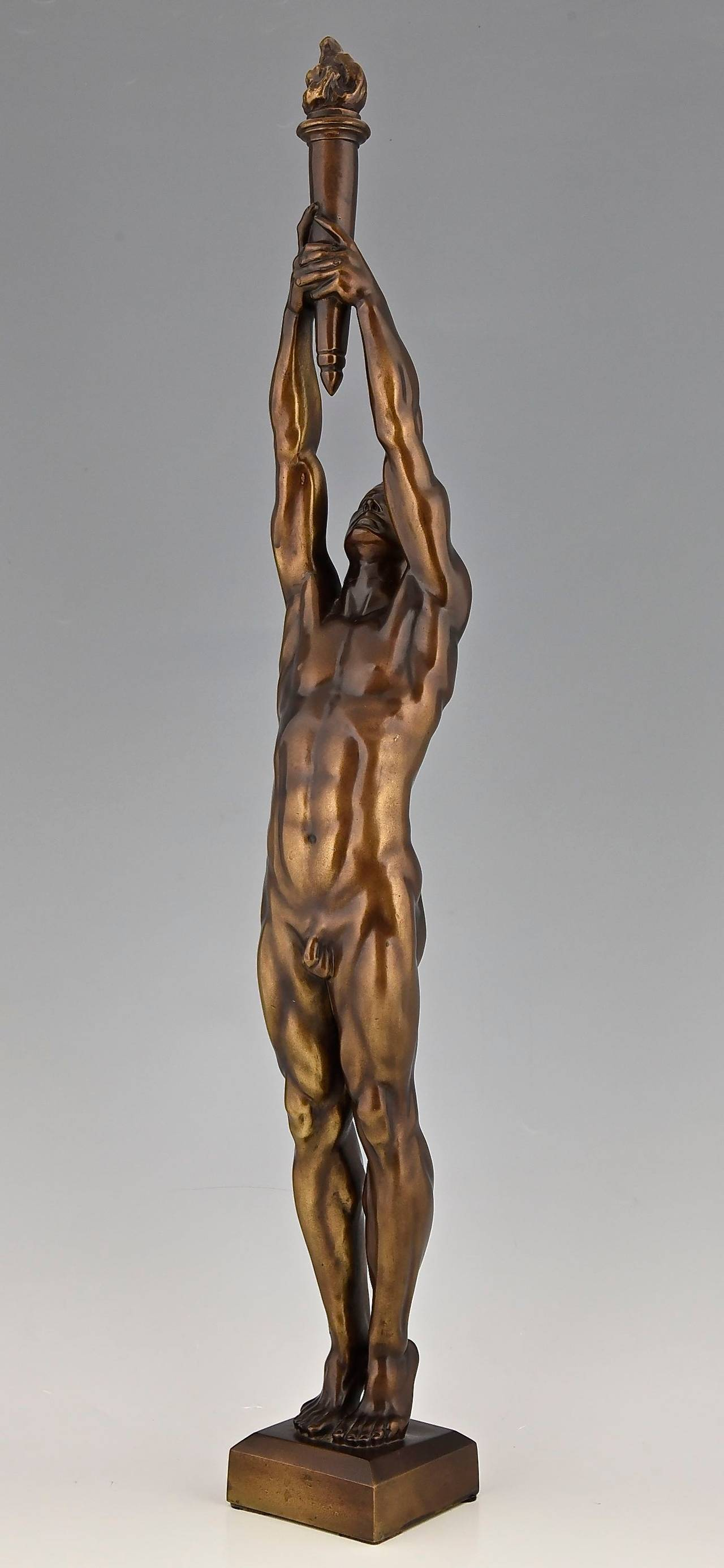 Bronze sculpture of a male nude holding a flaming torch.