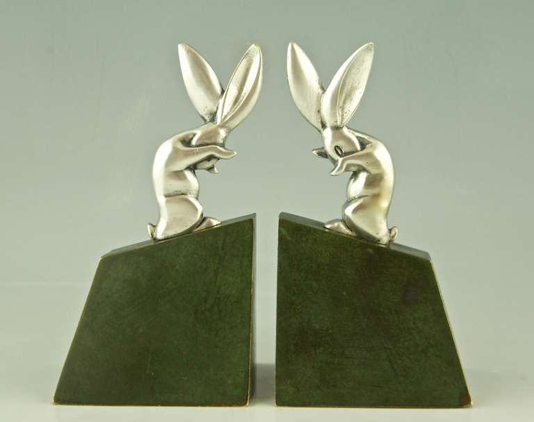A pair of bronze Art Deco rabbit or hare bookends.  By Henri Rischmann   Signature & Marks: H. Rischmann, Bronze.  Style: Art Deco. Date: Ca. 1925.  Material:  Bronze with silver patina for the hare.  Green patinated bronze for the base.