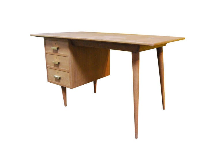 "Limewashed oak desk.  Three drawers with brass handles.  Stamped ""Producción - La Corrala - Madrid - Jose Peuva"""
