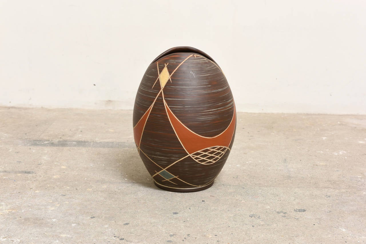 A gorgeous handmade vase of red clay by Ilkra Edelkeramik,  Ransbach-Baumbach, West Germany. A beautiful handmade vase with horizontal rings in Sgraffito technique and abstract decoration in white, yellow and blue.  The vase is in excellent