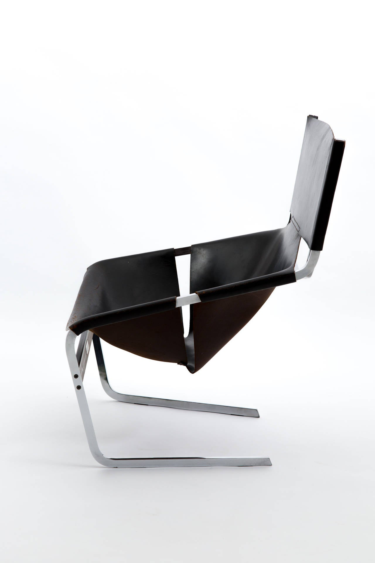 The F444 designed in 1963 by Pierre Paulin for Artifort. Bent and chrome-plated iron frame, linking rail between legs from sprayed rectangular section steel. Seat and backrest from saddle leather joined together. The chair has a metal mark with
