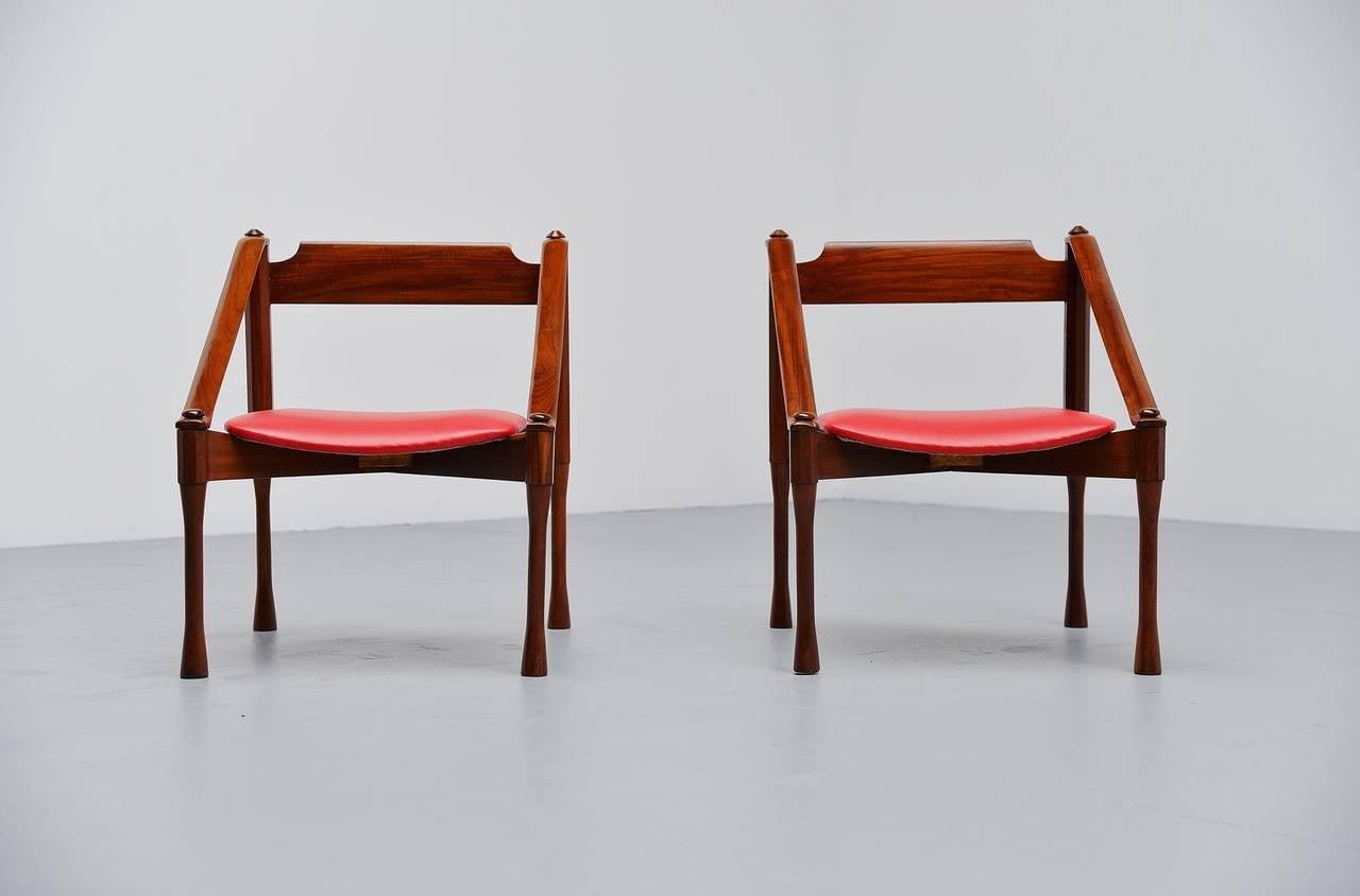 Amazing pair of lounge chairs designed by Giulio Moscatelli for Moscatelli, Italy 1950. These chairs are made of solid Italian walnut wood and have their original red vinyl seats. The chairs are amazing shaped and crafted into a very uncommon shape