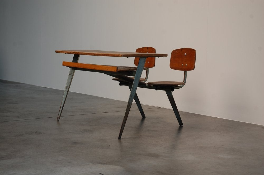 Important double school desk type 'Compass' No.850 designed by Jean Prouve (1901-1984) for Ateliers Jean Prouve in 1952. Rectangular wooden desk top, with magazine shelve below rests on 4 bent steel feet which support the top and a tubular frame