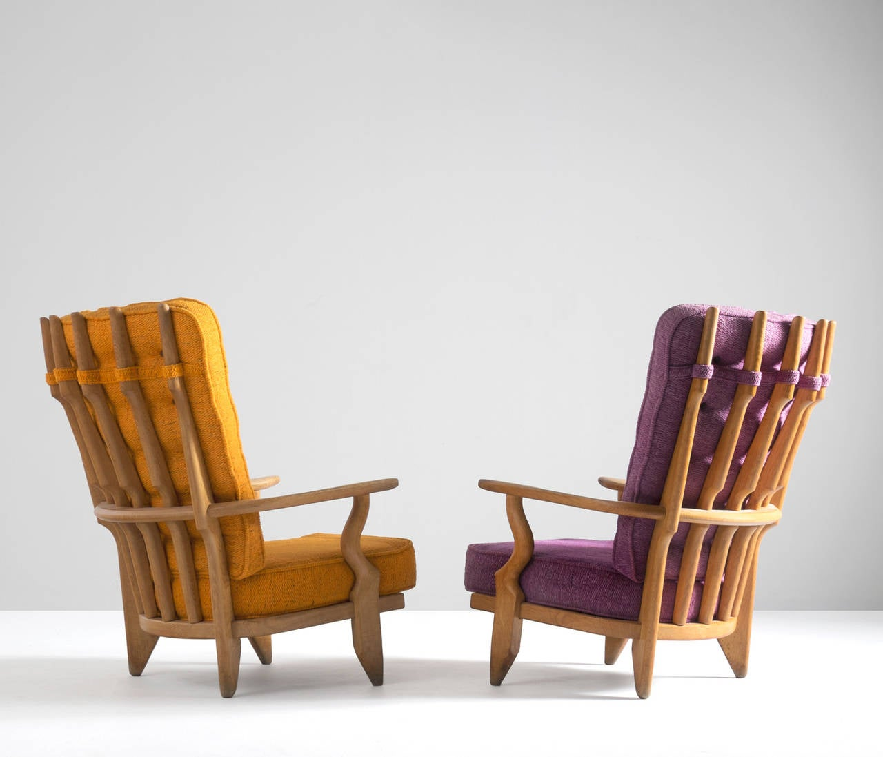Two extraordinary French Guillerme & Chambron high back lounge chairs in solid oak with the typical characteristic decorative details at the backs. 