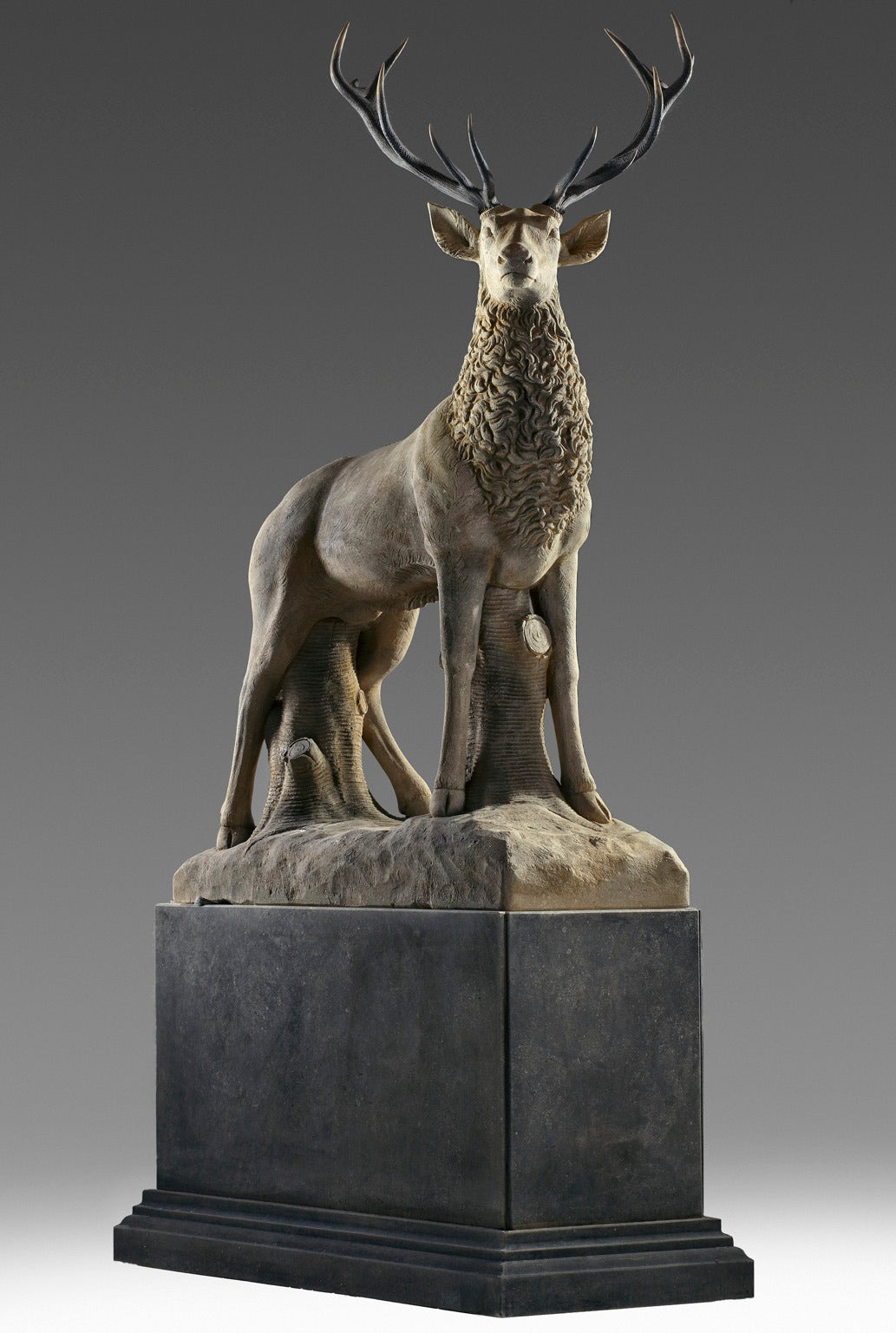 Naturalistically modelled standing, above a rectangular section limestone plinth, 325 cm. high overall, the base 100 cm. high.