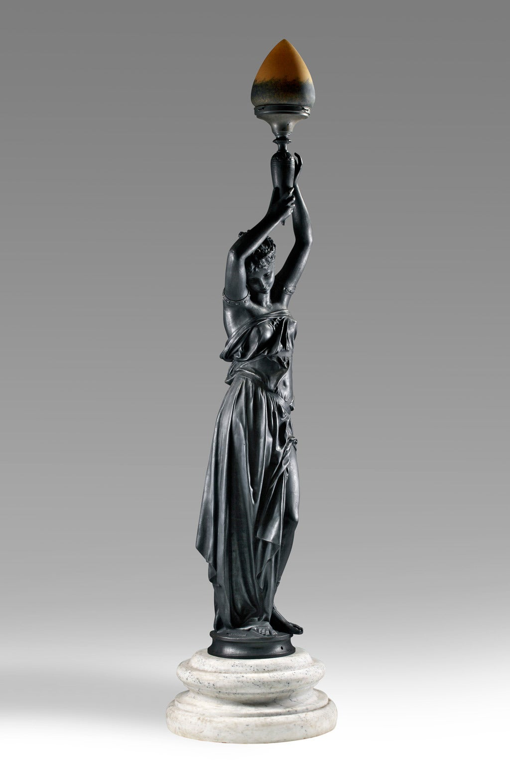 Cast by the Durenne Foundry, the maiden portrayed as standing and draped in the classical manner, the torchere held aloft above her head, on a waisted marble socle.