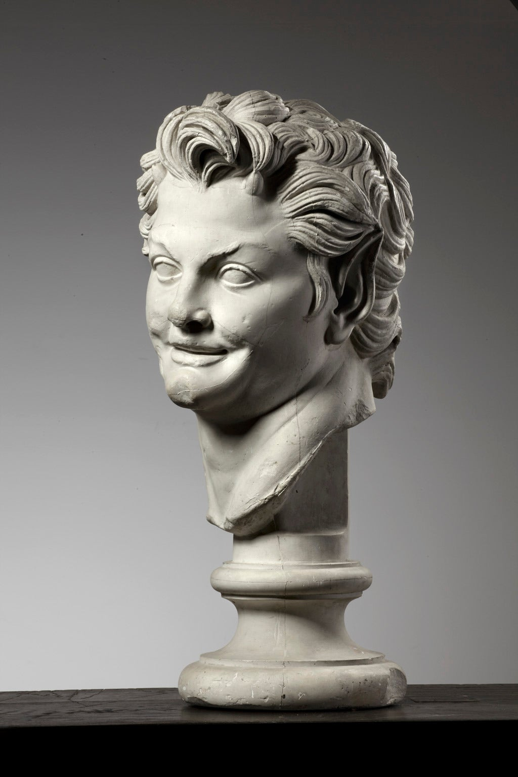 A large plaster bust of a young man on a socket.