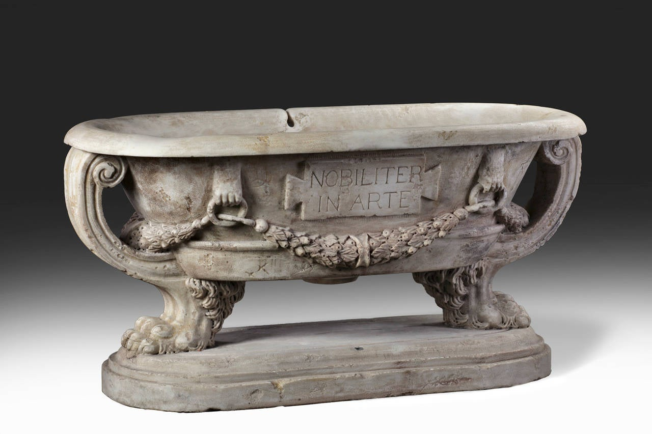 Planter of oval section, with everted rim, the long sides with laurel swags in high relief, the front with a tablet inscribed 'Magistri Romani,' with an openwork scrolling support at each end, above four paw feet, on an oval socle.