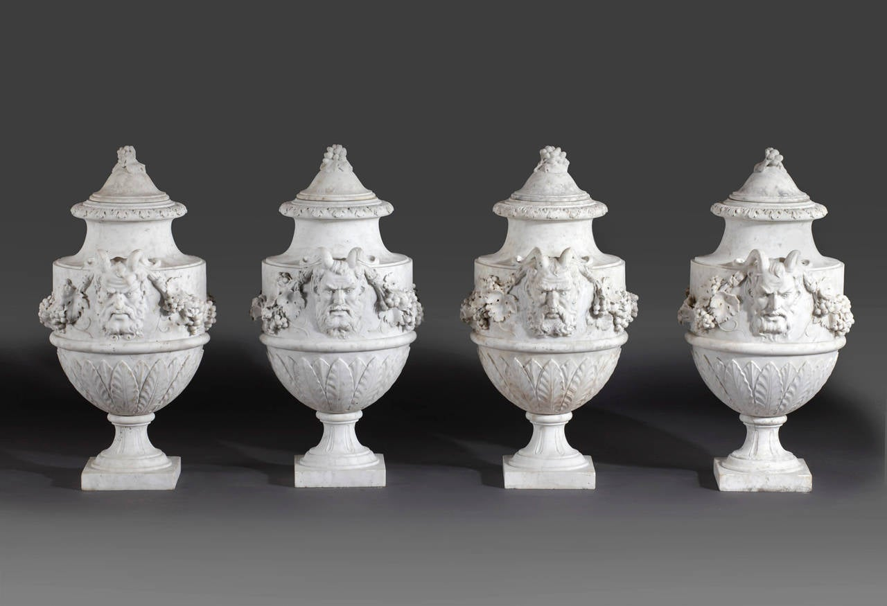 A set of French sculpted white marble vases in neoclassical style, late 19th century, each with domed top to a slender neck, above twin Bacchic masks united by foliate swags to each side, above leaf clasped undersides, waisted socles and square
