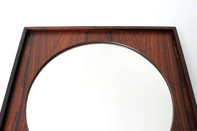 Petite rosewood mirror made in Sweden by glass master Markaryd. The mirror is housed inset into a finely figured rosewood or jacaranda frame.