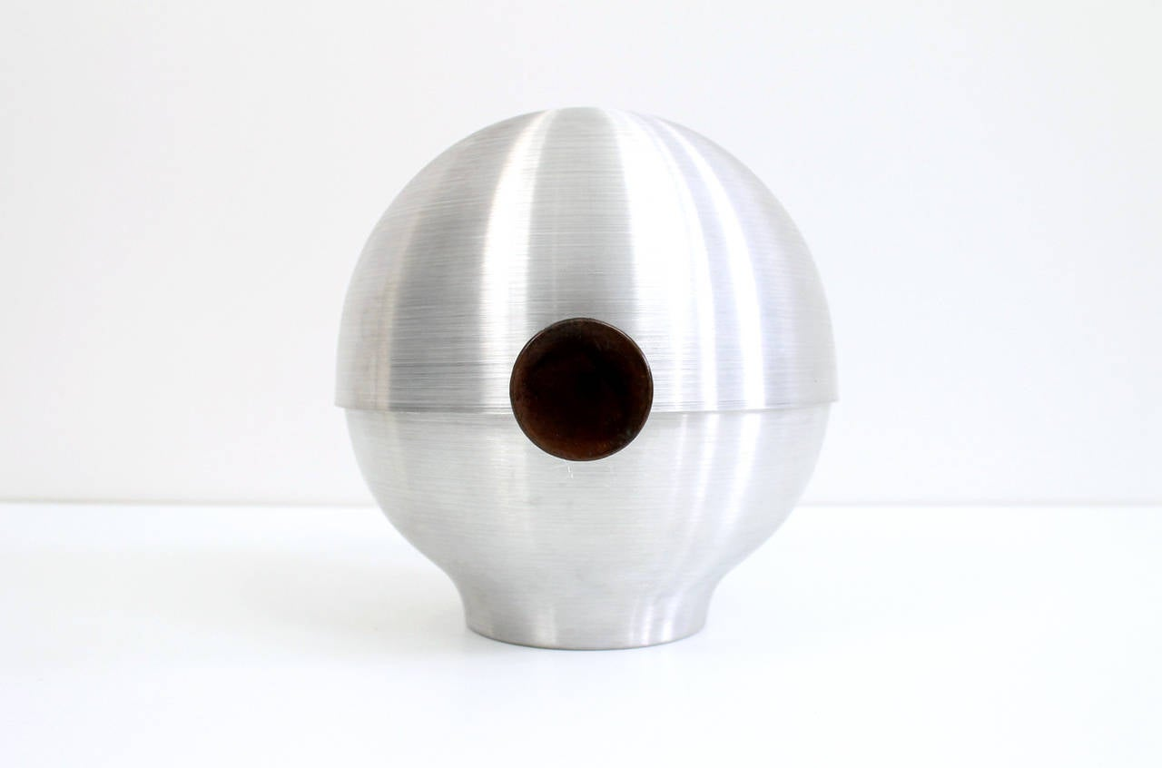 Early modernist spun aluminum vessel with tilting lid designed by Russel Wright for Metware. Originally marketed as a combination bun warmer, ice bucket, and fruit bowl. Strong machine age styling to this utilitarian object. Knobs of heat resistant