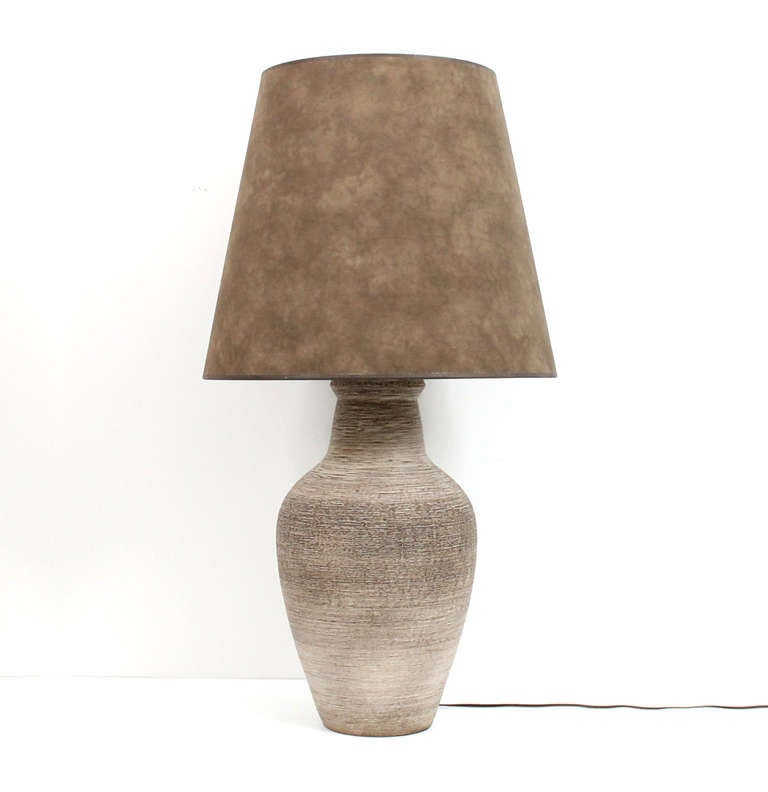 Large-scale ceramic table lamp by Lee Rosen for Design Technics. Lamp implements a unique striated circular design on the vase shaped body. Includes a custom suede shade. We have this lamp pictured in a period Design Technics catalog. Dimensions of